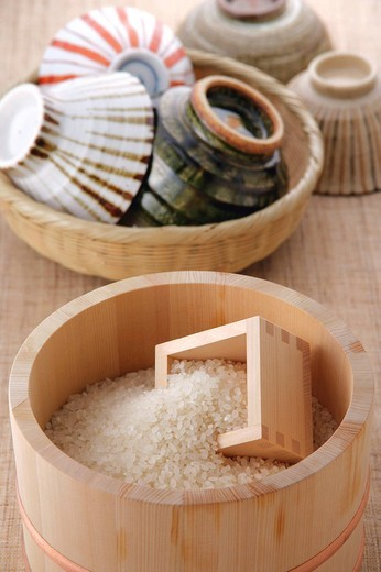 Stock Photo: 1436R-321486 Uncooked rice in a bamboo tub and rice bowls