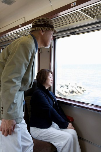 Senior couple looking out train window : Stock Photo