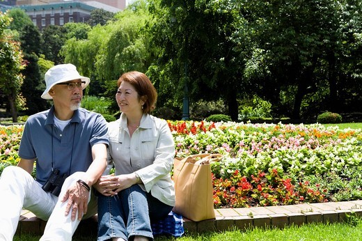 Senior couple sitting by flower bed : Stock Photo