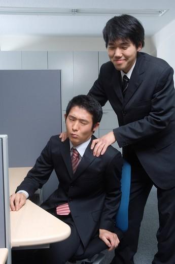 Businessman giving colleague shoulder massage : Stock Photo