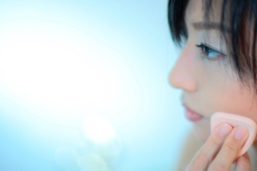 Profile of a young woman applying makeup, close_up : Stock Photo