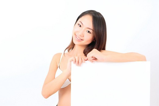 Stock Photo: 1436R-325882 Portrait of a young woman in bikini with blank message