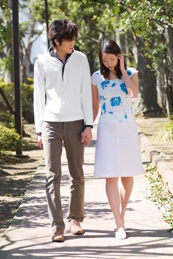 Stock Photo: 1436R-328341 Young couple walking in a park