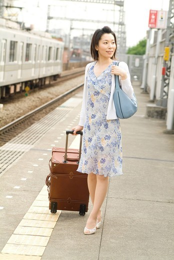 A mid adult woman walking with suitcase : Stock Photo