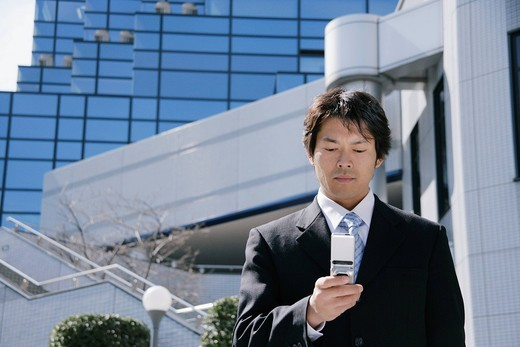 Stock Photo: 1436R-328556 A mid adult businessman looking at mobile phone