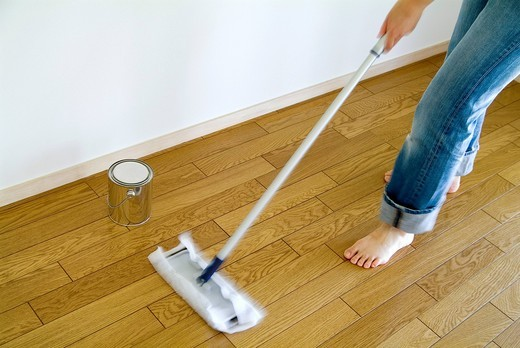A woman cleaning floor with mop, blurred motion : Stock Photo