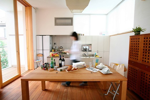A young woman walking in kitchen, blurred motion : Stock Photo