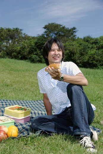A young man eating hot dog : Stock Photo