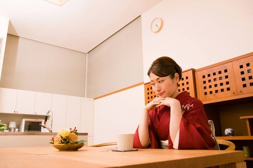 A young woman wearing kimono sitting in dining room : Stock Photo