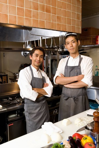 Stock Photo: 1436R-330019 Two chefs standing in restaurant kitchen