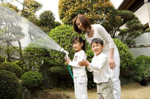 Mother and children watering trees : Stock Photo