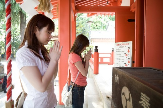 Two young women praying at shinto shrine : Stock Photo