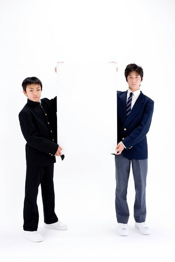 Two teenage boys holding blank message board : Stock Photo