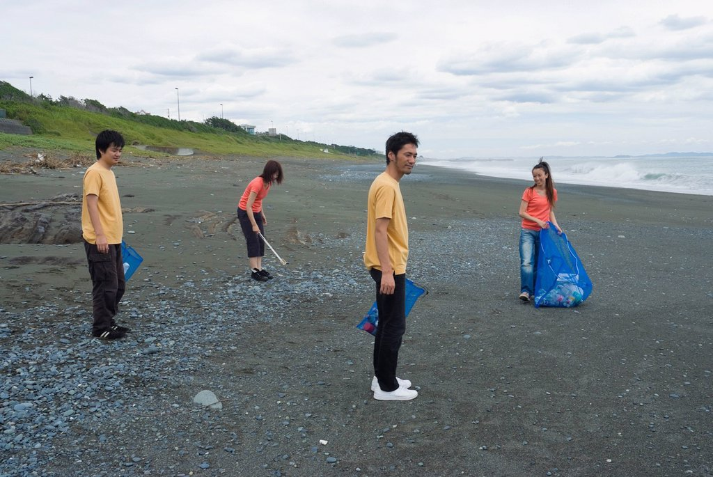 Stock Photo: 1436R-333224 Young people cleaning beach