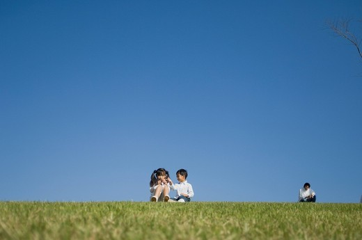 Stock Photo: 1436R-333751 Children playing in field with father sitting behind