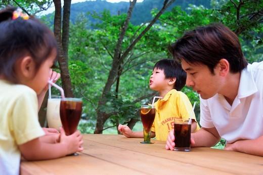 Stock Photo: 1436R-334907 Family drinking juice at terrace