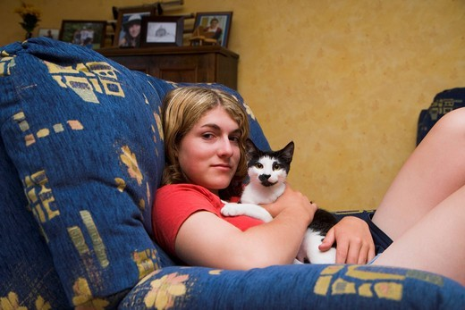 Stock Photo: 1436R-340470 Teen girl holding cat on sofa