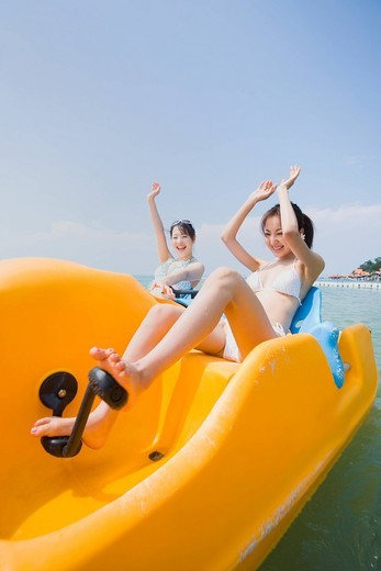 Stock Photo: 1436R-345301 Two young women riding on pedal boat