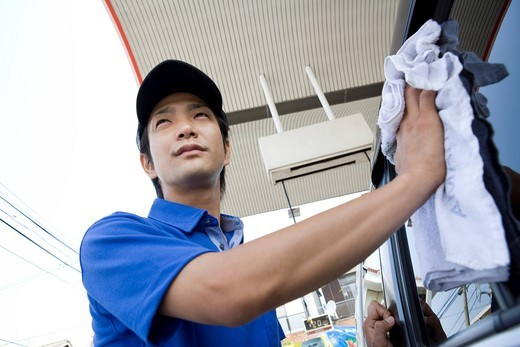 Stock Photo: 1436R-345509 Gas station clerk wiping car window