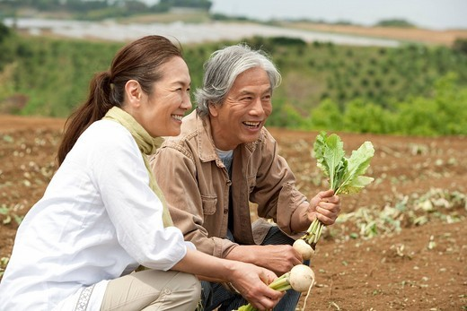 Stock Photo: 1436R-346403 Senior couple squatting on field