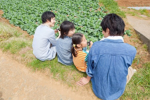 Family sitting on field : Stock Photo
