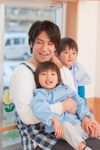 Kindergarten Teacher Holding Kids : Stock Photo