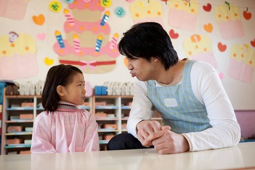 Kindergarten Teacher and Girl Making Face : Stock Photo