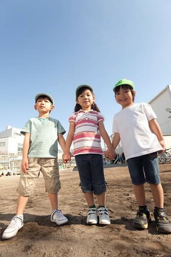 Three Children Standing at Playground : Stock Photo
