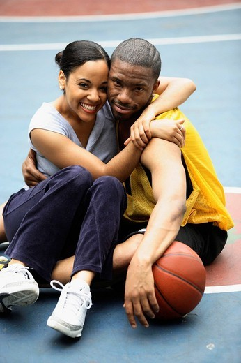 Stock Photo: 1436R-356008 African-American girlfriend and boyfriend hugging and smiling into camera