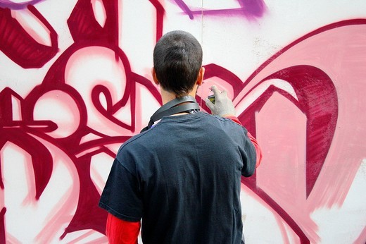 Young man painting a graffiti : Stock Photo