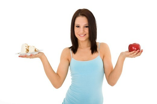 Stock Photo: 1436R-362412 Caucasian woman holding an apple and slice of cake trying to decide which one to eat