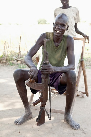 Dinka man cleaning ak-47 in Lilir Sudan, December 2010 : Stock Photo