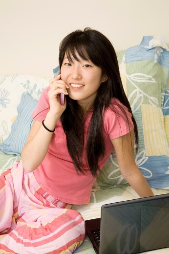 Stock Photo: 1436R-426699 Asian American teen working on laptop computer and talking on cell phone