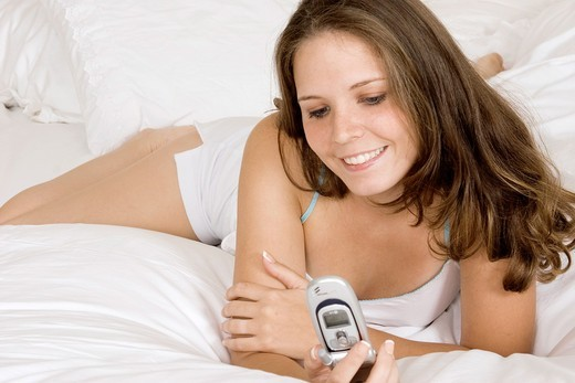 Stock Photo: 1436R-426810 Caucasian woman in early 20´s laying in bed talking on cell phone