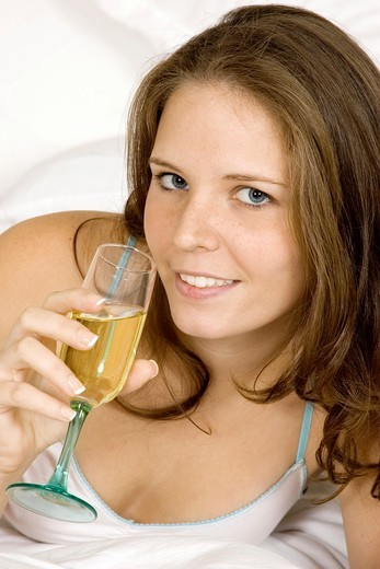 Caucasian woman in early 20´s laying in bed with a glass of White Wine : Stock Photo