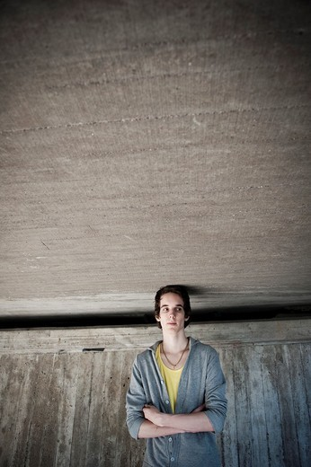 Stock Photo: 1436R-427063 Moody young man in front of concrete wall