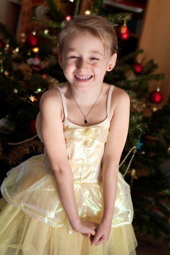 Little girl in a princess costume next to a Christmas tree : Stock Photo