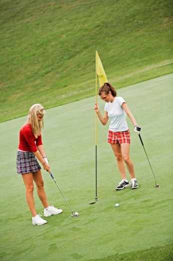 Women in their early 20s playing golf : Stock Photo