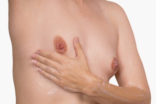 Caucasian woman performing a breast cancer examination : Stock Photo