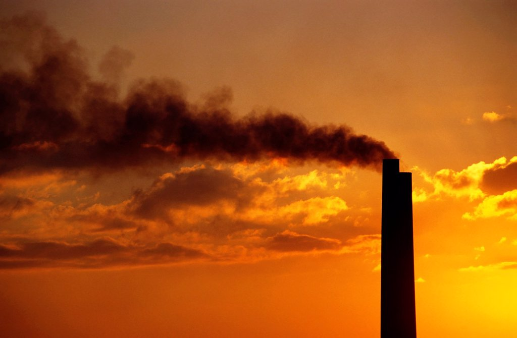 Stock Photo: 1436R-429145 Silhouetted smoking chimney at sunset, Berre, France