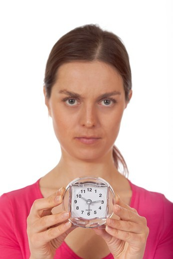 A young woman holding an alarm clock : Stock Photo