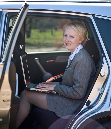 Happy Smiling Businesswoman With Laptop Computer Sitting in Car : Stock Photo
