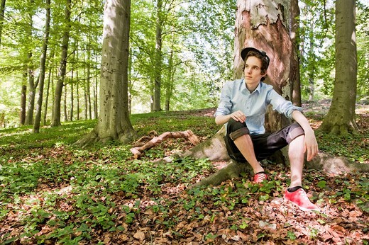 Stock Photo: 1436R-429537 Young man sitting in front of a tree in the woods
