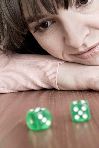 Young woman looking at a pair of green dice : Stock Photo