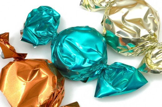 Stock Photo: 1436R-430490 Colourful shiny paper wrapped toffee sweets on white background