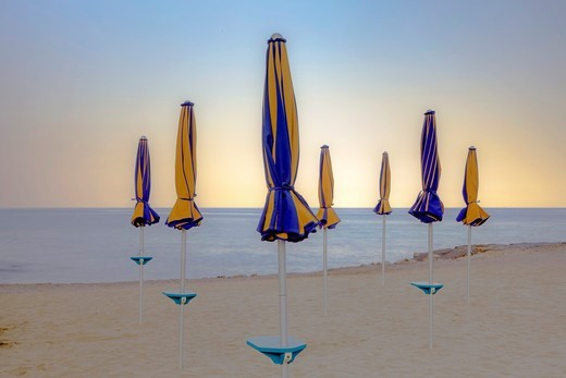 closed umbrellas at the beach of the Mediterranean Sea at sunset, Italy : Stock Photo