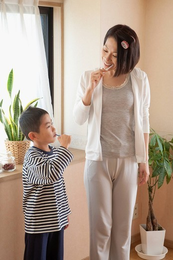 Mother and son brushing teeth together : Stock Photo