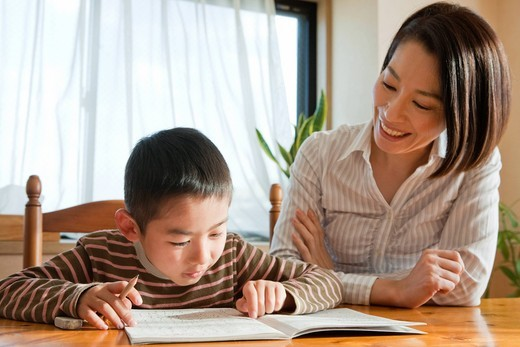 Mother helping son with homework : Stock Photo