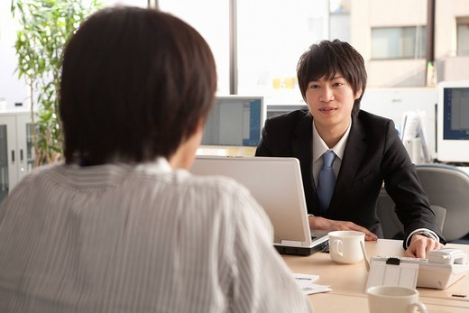 Young businessman talking to coworker : Stock Photo