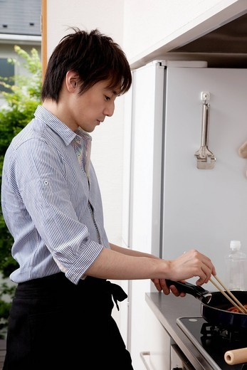 Stock Photo: 1436R-433705 Young man cooking in the kitchen
